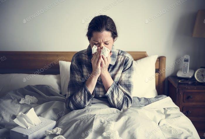Eine Frau, die an Grippe im Bett leidet