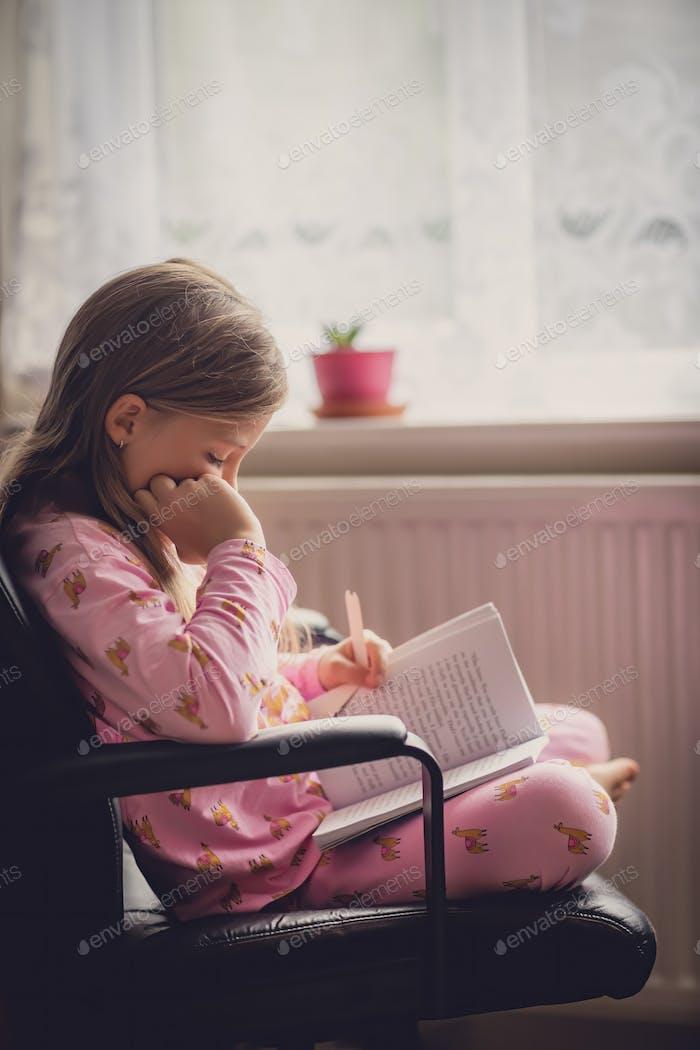 Girl in pyjama reading a book