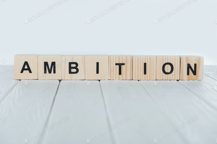 close up view of ambition word made of wooden cubes on white wooden tabletop