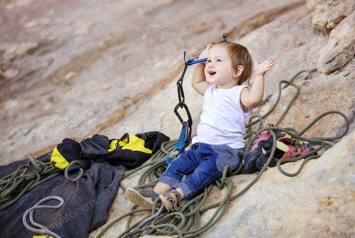 Little girl playing with rock climbing gear
