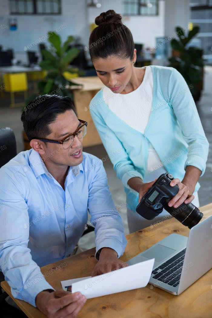 Businesswoman showing digital camera to colleague