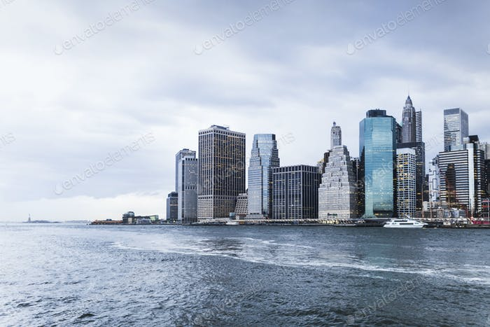 Scenic view of East River and city against cloudy sky