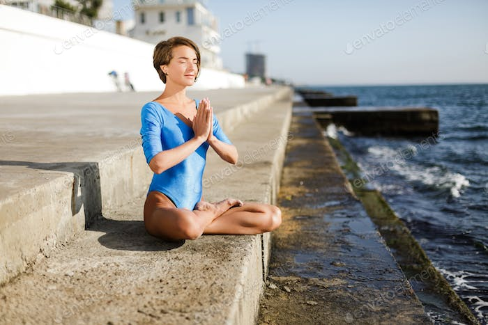 Woman sitting in lotus pose and dreamily closing her eyes meditating by the sea