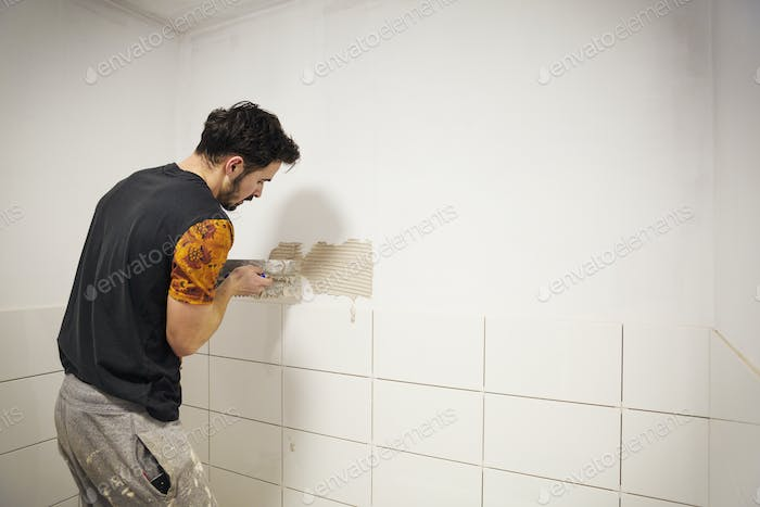 A builder, tiler placing white ceramic tiles on a wall in a bathroom.