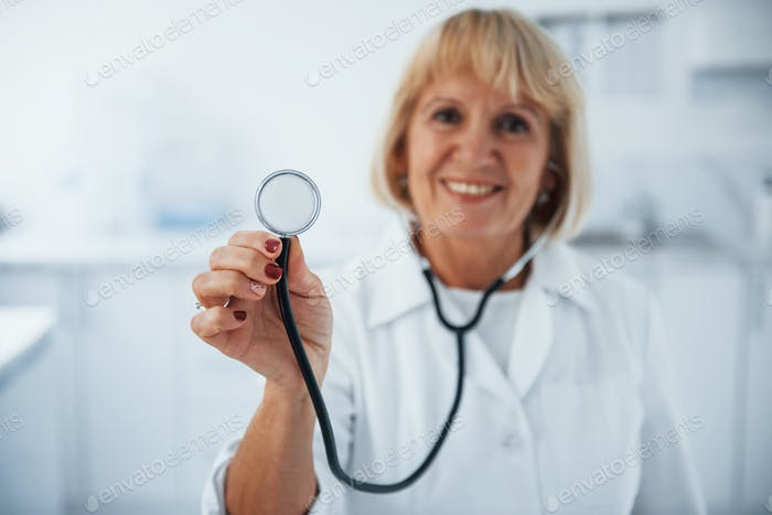 Holds stethoscope in hand. Portrait of senior doctor in white uniform that stands in the clinic