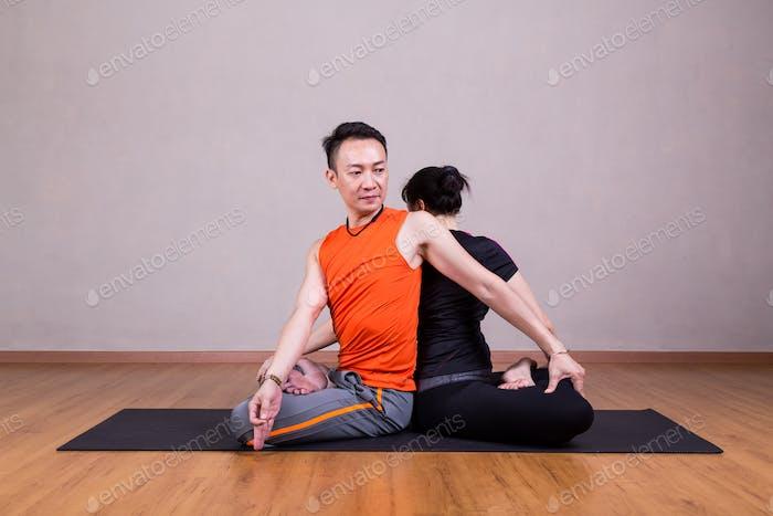 Pareja Twist Yoga Pose por una pareja