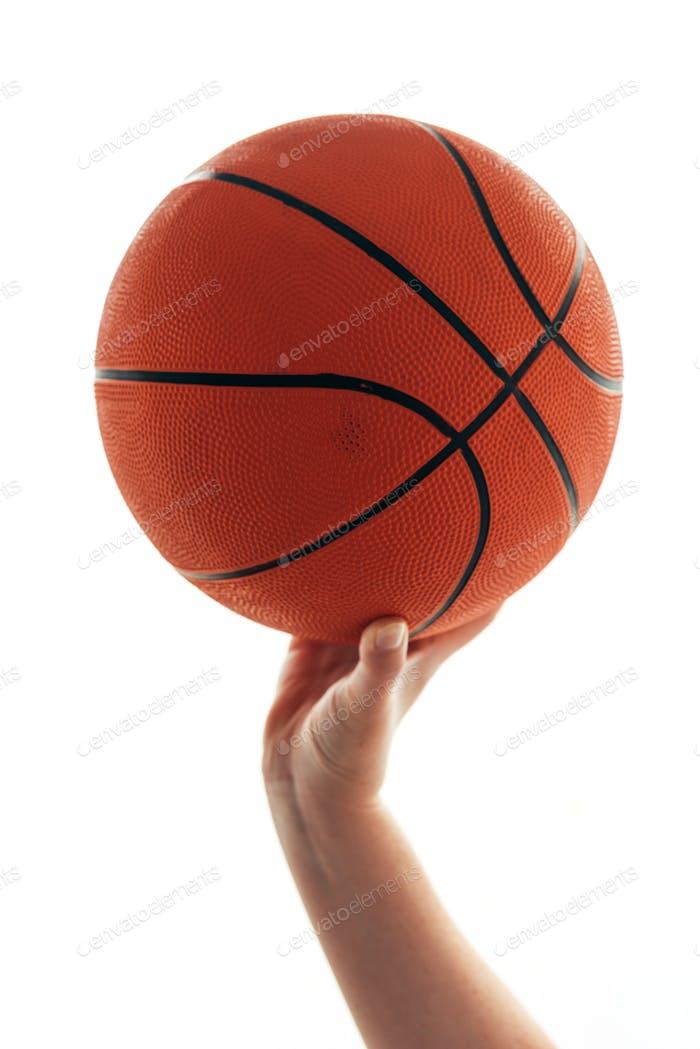 Female hand with basketball ball isolated on white background