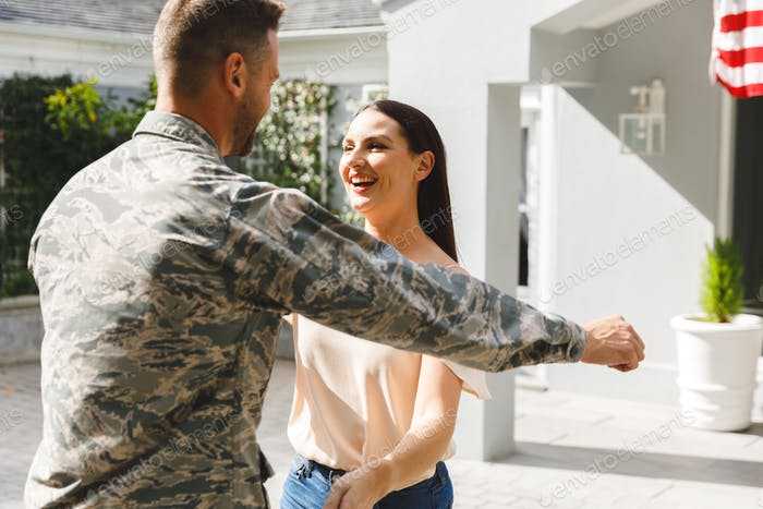 Caucasian male soldier hugging wife outside house decorated with american flag