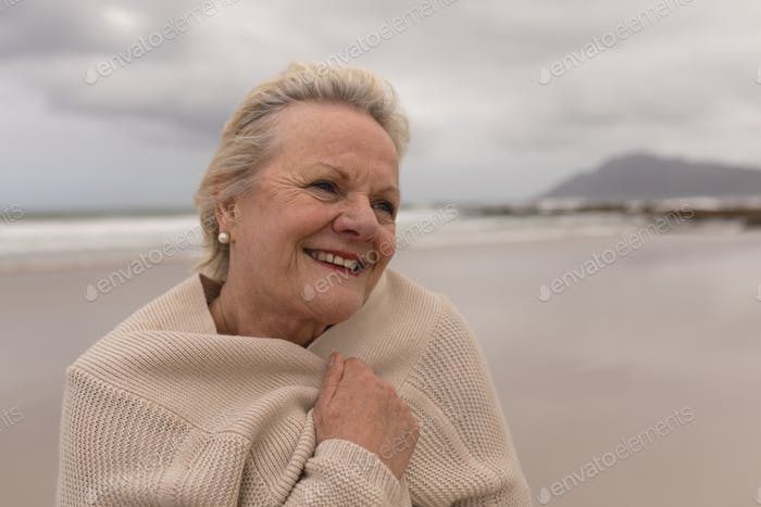 Happy active senior woman wrapped in jumper on the beach
