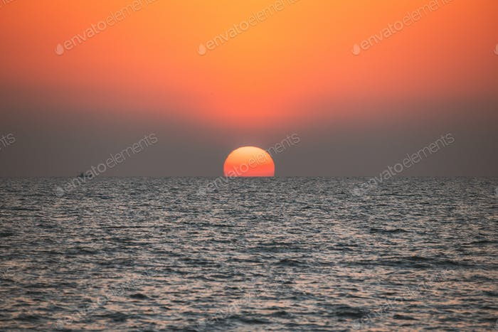Sundown Above Sea Horizon At Sunset. Natural Sunrise Sky Warm Colors Over Ocean