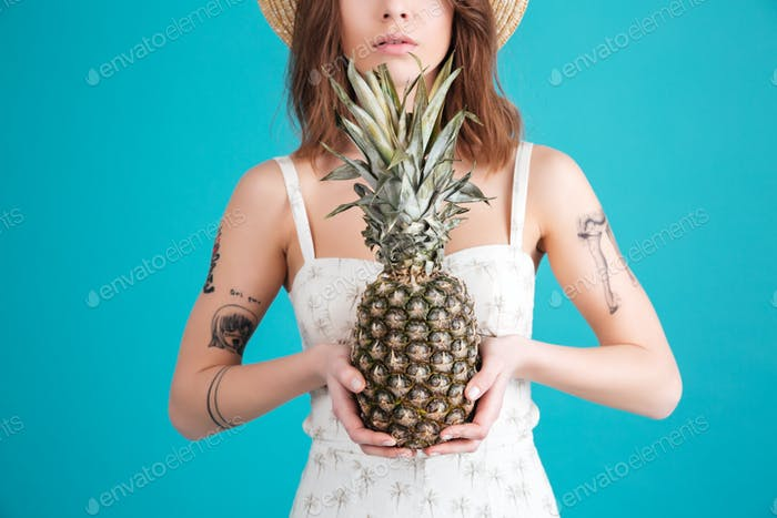 Cropped picture of serious young lady holding pineapple.
