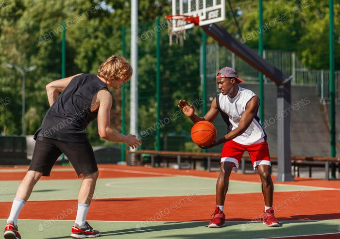 Two millennial sportsmen playing basketball at outdoor arena on summer day