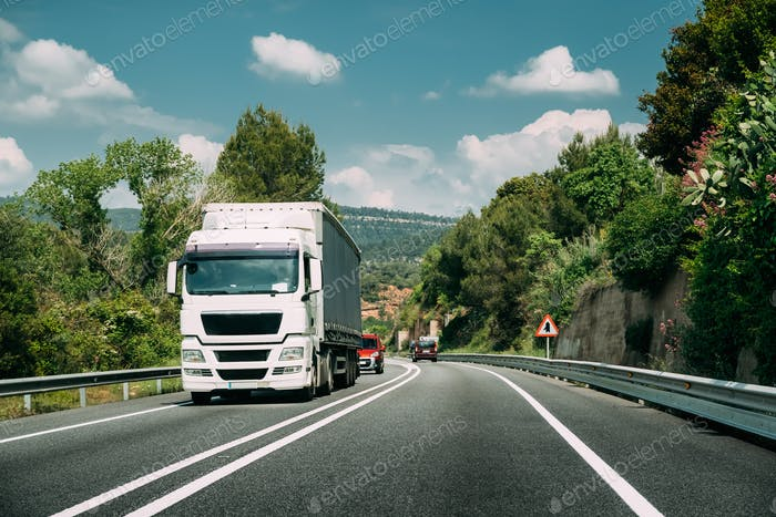 White Truck Or Tractor Unit, Prime Mover, Traction Unit In Motion On Road, Freeway. Asphalt Motorway