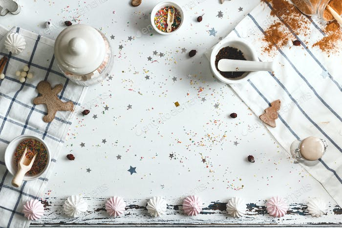 White table, strewn with candy powder and various holiday sweets around the center. Space for text.