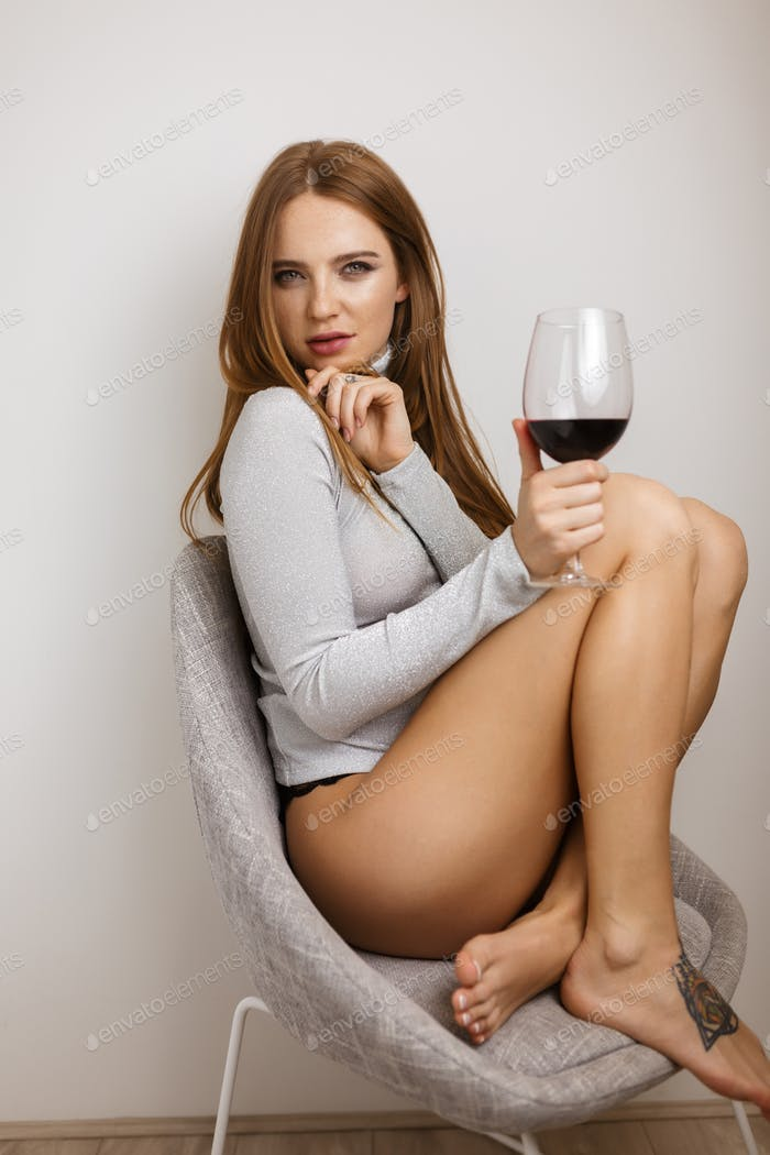 Beautiful lady sitting in chair with glass of red wine in hand and thoughtfully looking in camera