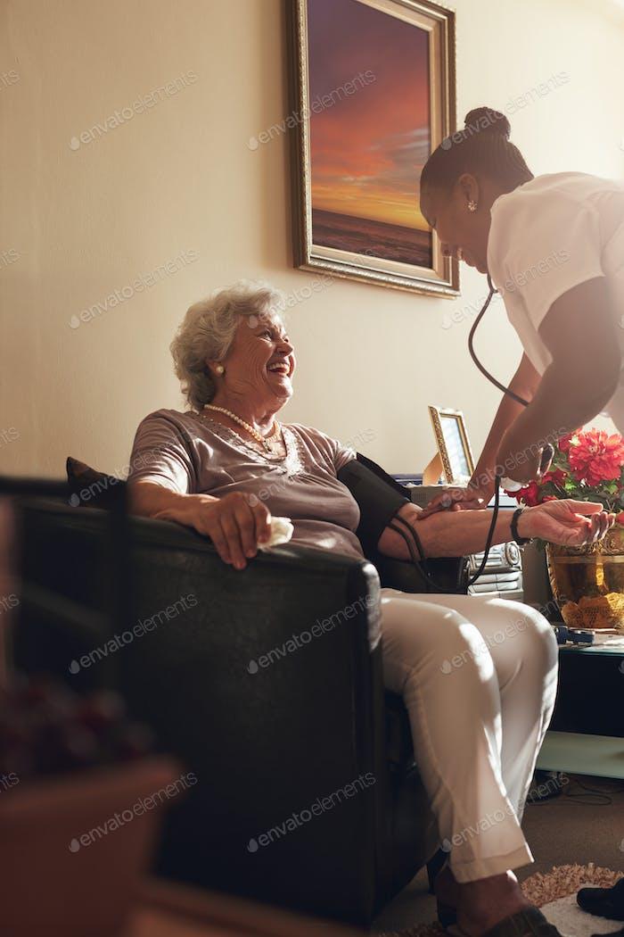 Nurse measuring blood pressure of senior lady patient