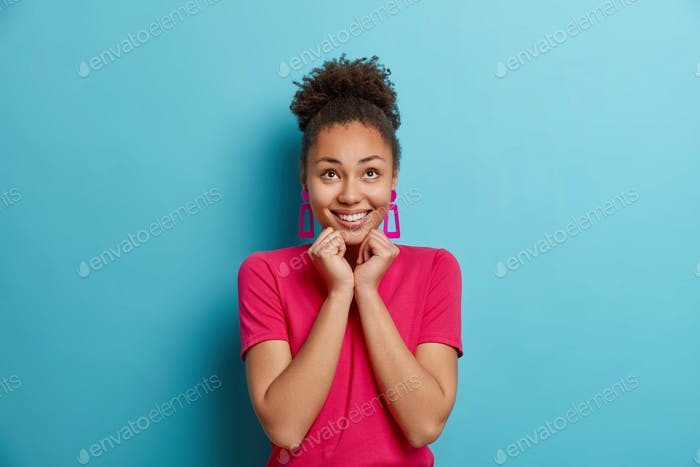 Joyful young Afro American woman keeps hands under chin concentrated above with enjoyment has dreamy