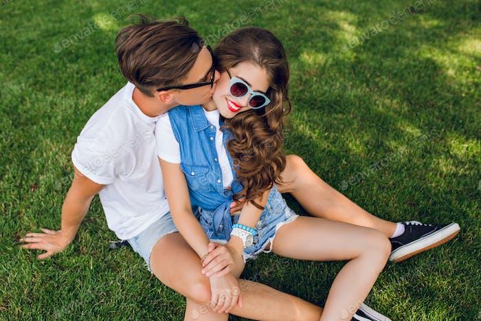 Nettes paar junge Leute auf Gras im Park. Schöner Kerl im weißen T-Shirt küsst Mädchen mit lon