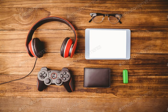 Tablet music headphone wallet glasses and US key on wooden table