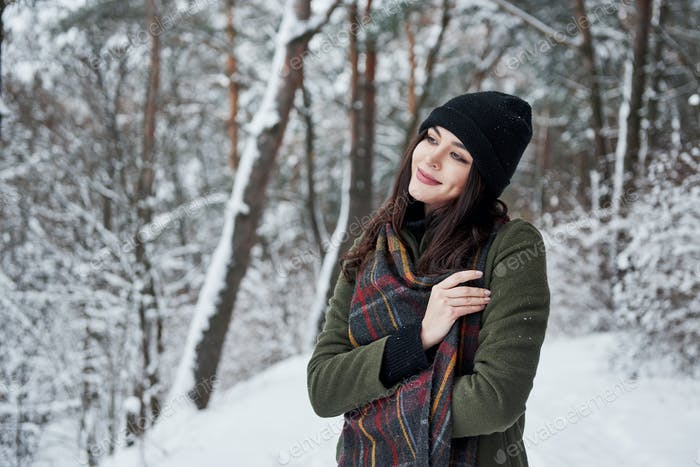Feeling joy. Cheerful young girl in warm clothes have a walk in the winter forest at daytime