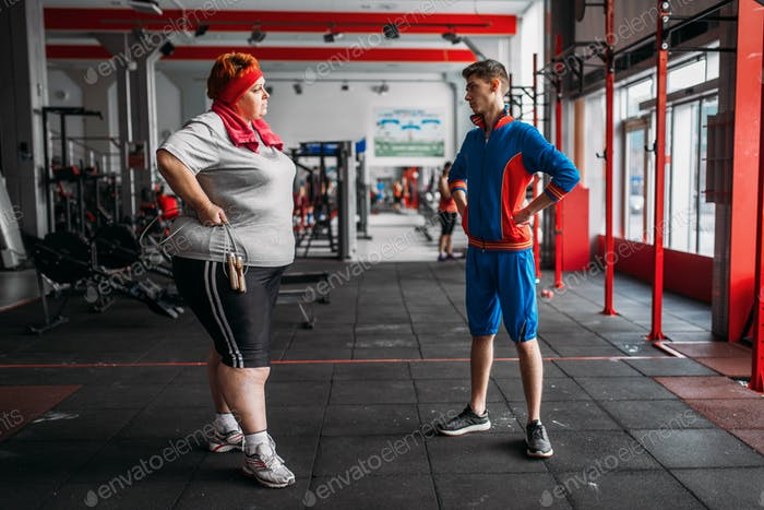 Fat woman talks with instructor after exercise