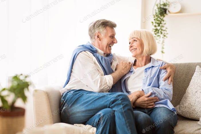 Senior affectionate couple relaxing on sofa at home