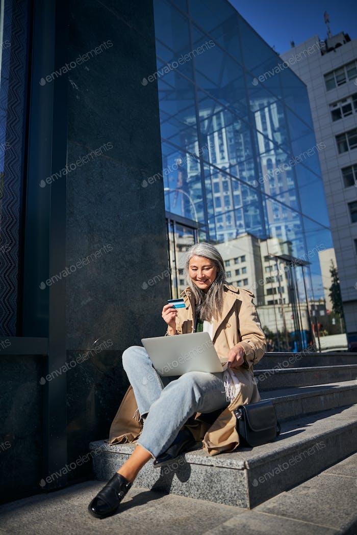 Fröhliche Frau mit Kreditkarte mit Laptops für Online-Shopping