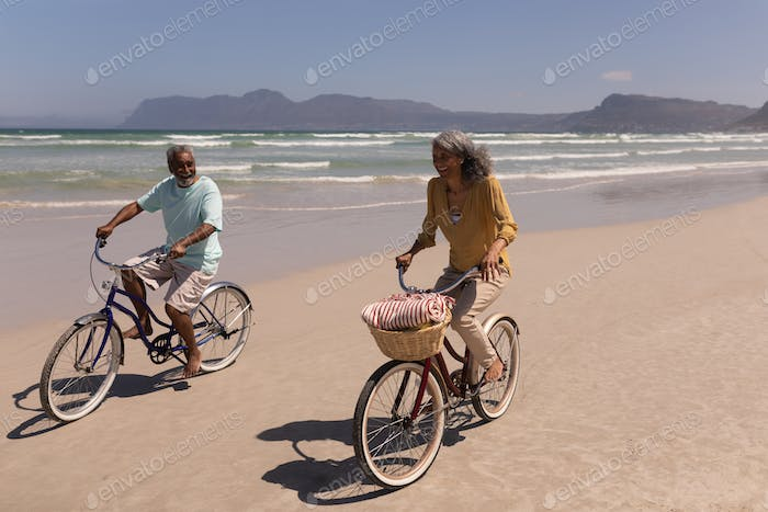 Happy senior couple riding bicycle on beach in the sunshine with mountains in the background