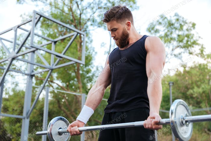 Serious young bearded fitness man lifting barbell