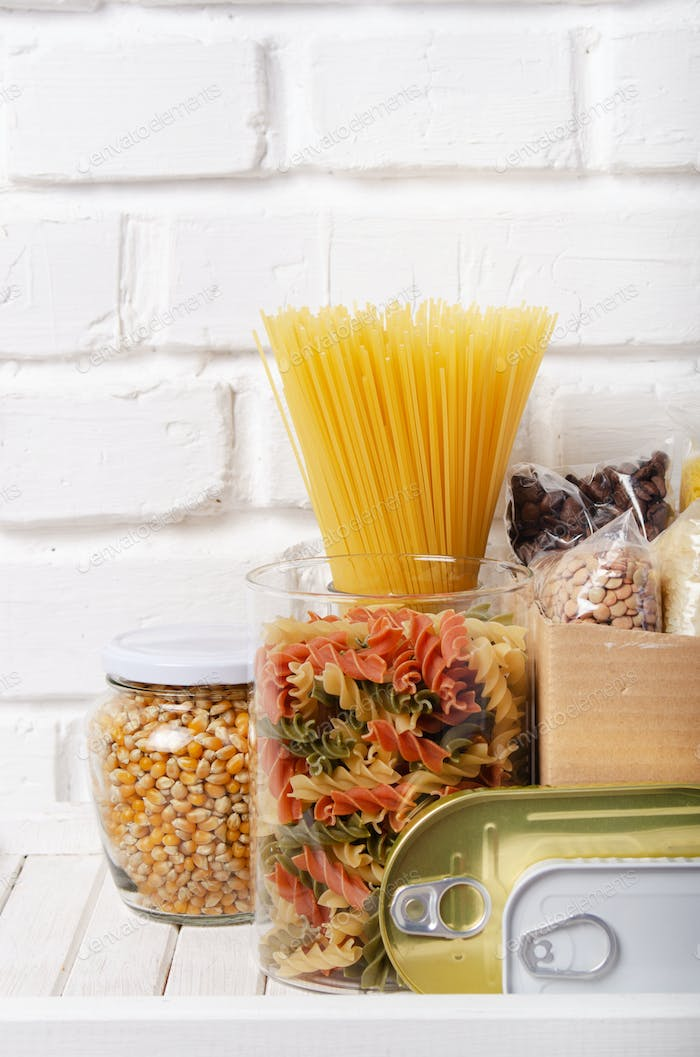 Set of uncooked foods on pantry shelf prepared for disaster emergency conditions closeup view
