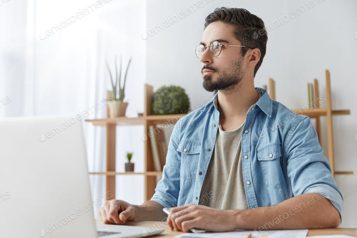 Thoughtful young copywriter being deep in thoughts, sits in front of opened laptop, thinks on creati