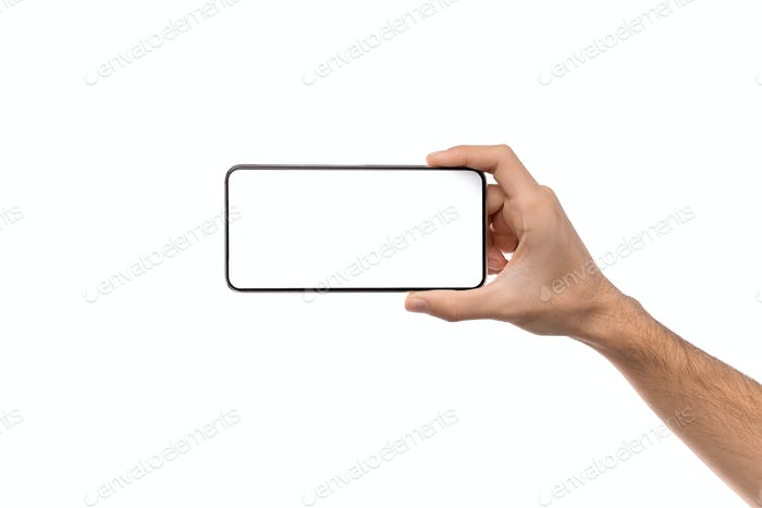 Man's hand holding modern smartphone with blank screen for mockup
