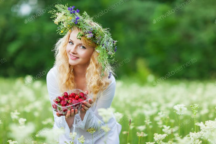 Young beautiful blond woman in white dress and floral wreath holding box of fresh strawberries on