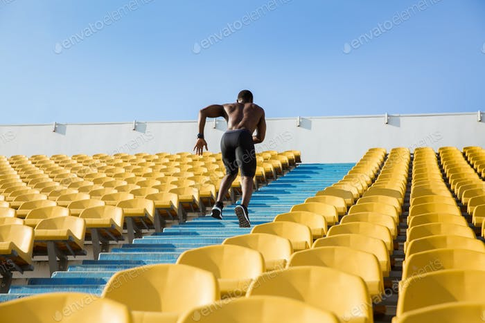 Back view of a male athlete exercising by running upstairs