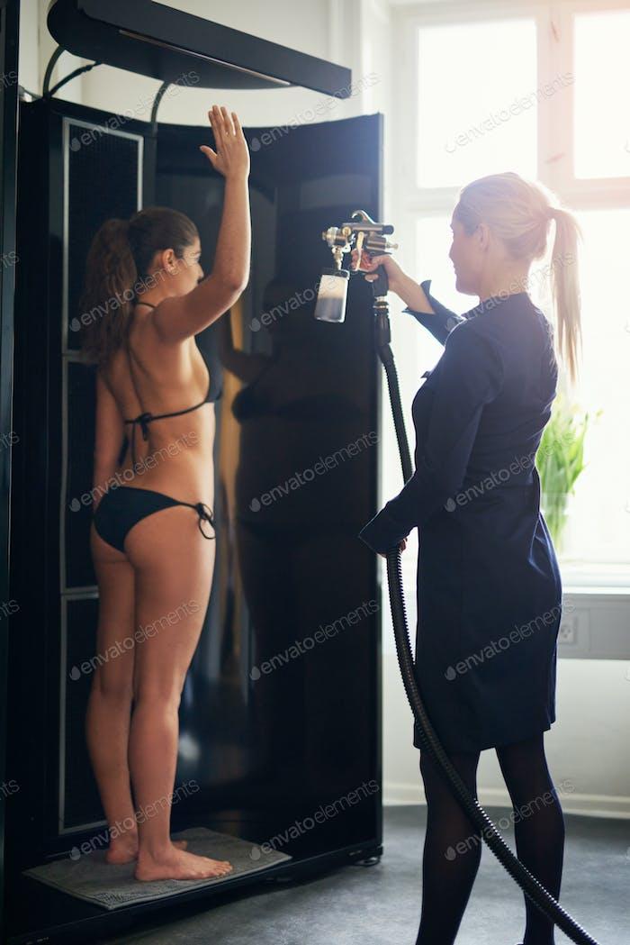 Cosmetologist spraying tan on woman in salon