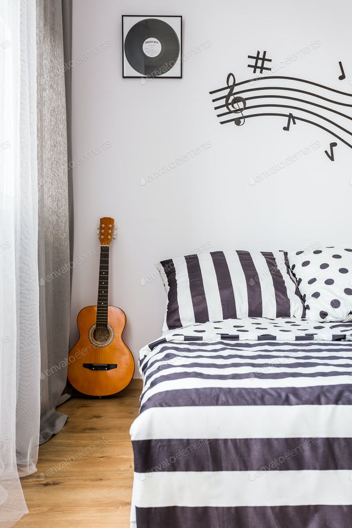 Bedroom with a guitar next to the bed