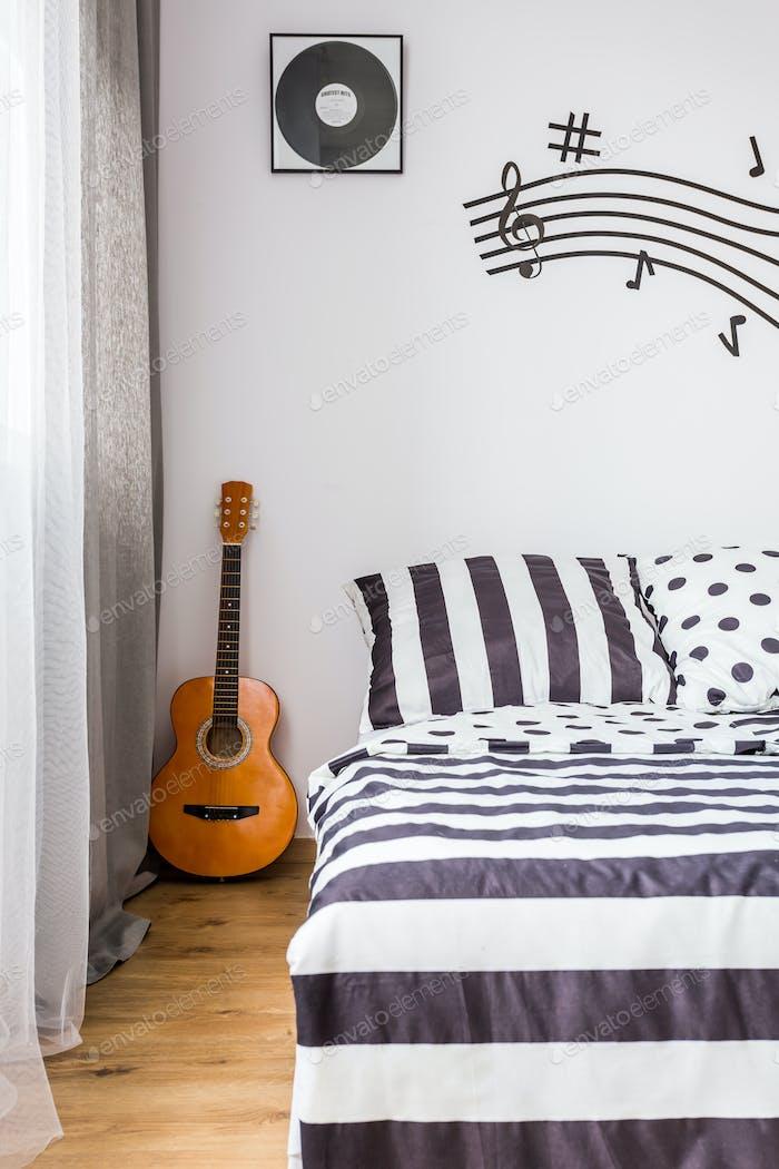 Schlafzimmer mit einer Gitarre neben dem Bett