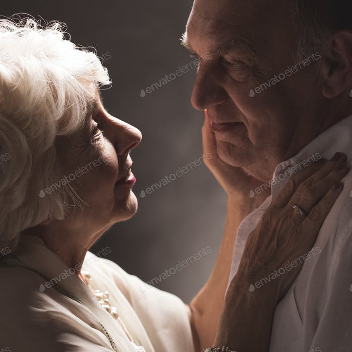 Senior woman touching husband's face