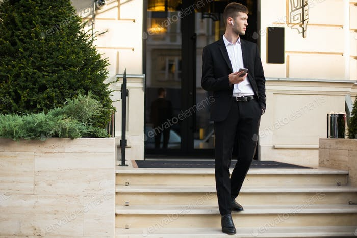 Young handsome man in black suit and white shirt with wireless e
