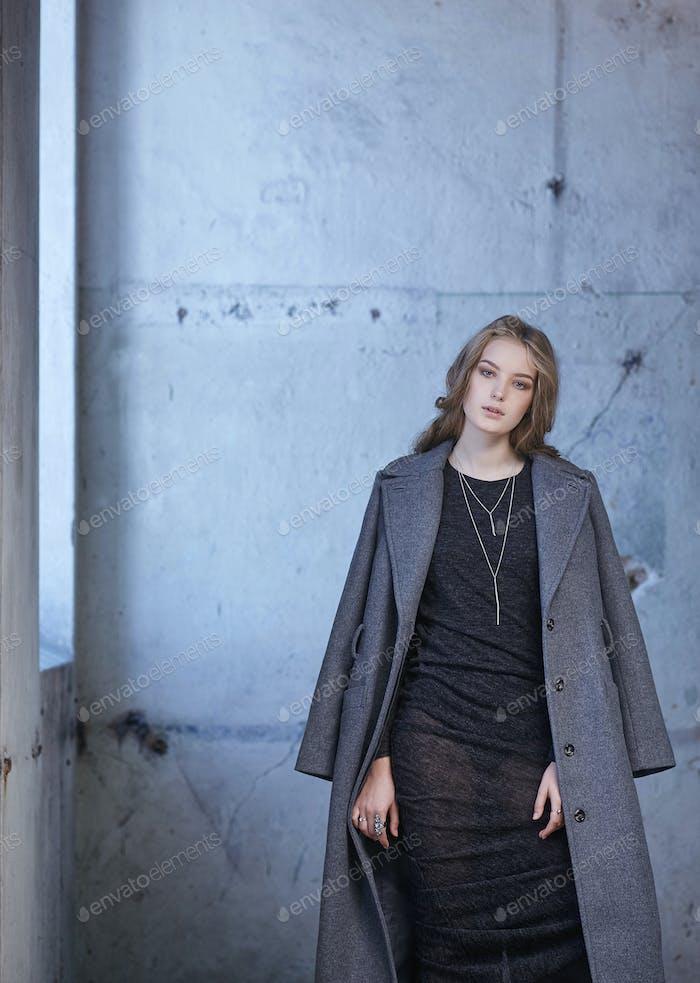 A  lady in a long grey jacket.