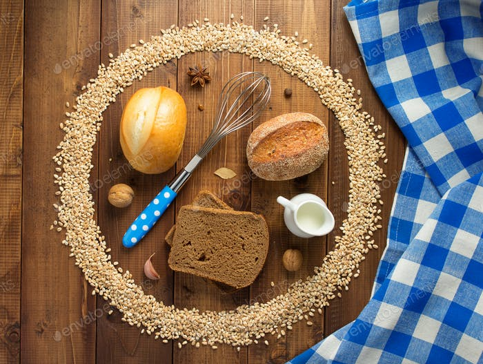wheat grains and bakery ingredients on wood