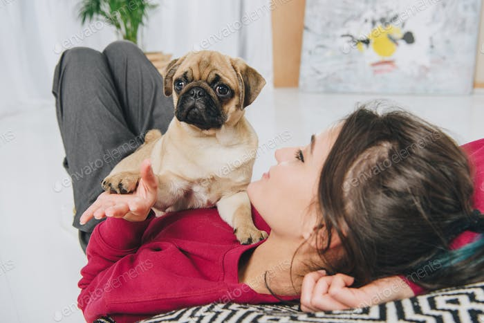 Young woman playing with pug puppy