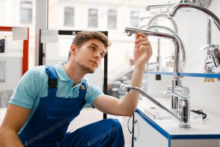 Fontanero en uniforme en escaparate en fontanería