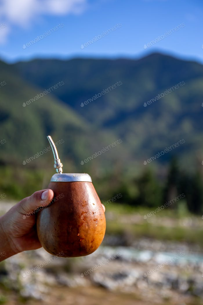 Man holding calabash yerba mate in nature. Travel and adventure concept. Latin American drink yerba