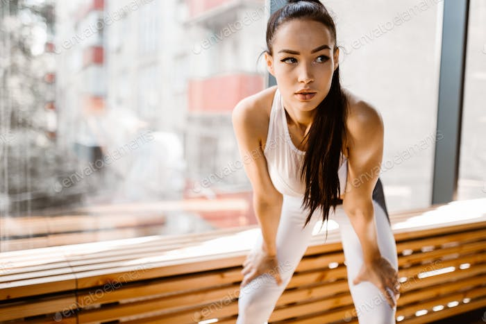 Beautiful slim dark-haired girl dressed in white sports clothes stands with her hand on the knees