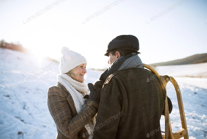 Beautiful senior couple carrying sled, sunny winter day.