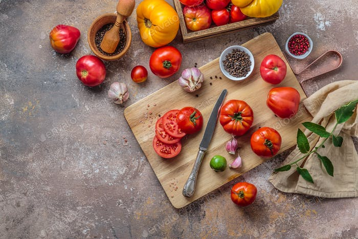 Ripe tomatoes on cutting board with knife, top view copy space