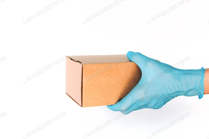 Contactless delivery, online shopping concept. Hand in medical glove gives craft box over blue