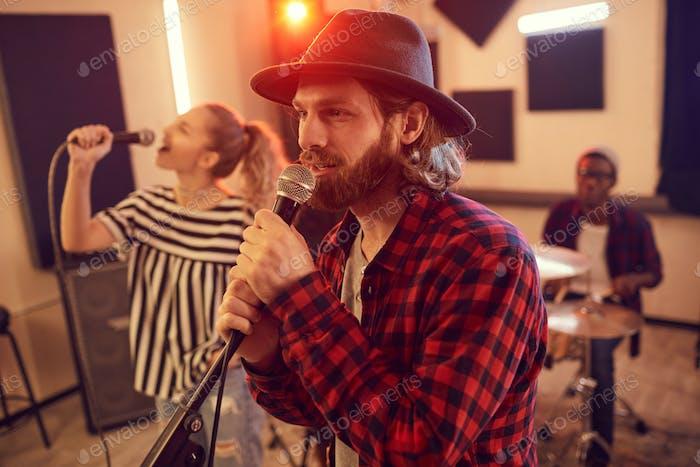 Bärtiger junger Mann singt mit Band