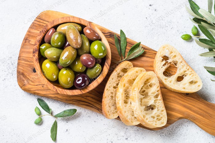 Olives and ciabatta on white background